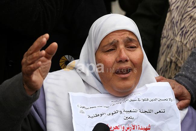 The mother of Jawaher Abu Rahmah shout slogans as she cries attending her daughter's funeral at the West Bank Village of Bil'in, on 01 January 2011. Jawaher, 36, who was protesting against Israel's West Bank separation barrier, was evacuated to the Ramallah hospital on 31 December 2010 after inhaling massive amounts of tear-gas during the weekly Friday protest in Bilin, and died on 01 January 2011 morning after she did not respond to medical treatment. Abu Rahmah was the sister of Bassem Abu Rahmah, who was killed during a protest in the same village, which is located about four kilometres from the Israel-West Bank border on 17 April 2009. Photo by Issam Rimawi