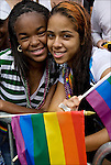 African American and Hispanic American lesbian couple with pride flag part of the faces in the crowd watching the Gay Pride Parade