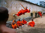 01381_20; Shaolin Monastery, Hunan Province, China; 2004; CHINA-10038NF3. A young monk runs along the wall over his peers.<br />
