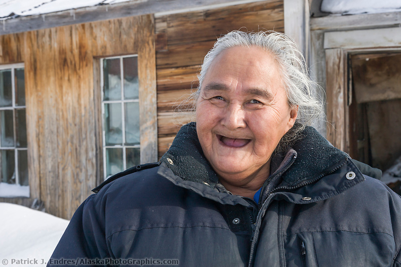 Annie Kirk from the native village of Buckland, poses in front of an old cabin in the ghost town of Candle, Alaska, the half way point of the 2008 All Alaska Sweepstakes sled dog race.