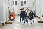 """Displaced children run among """"caravans,"""" manufactured housing units for displaced families, in the village of Bakhtme, Iraq. The community was flooded with displaced families when the Islamic State group took over nearby portions of the Nineveh Plains in 2014. The community includes a """"child-friendly space"""" sponsored by the Christian Aid Program Nohadra - Iraq (CAPNI), offering displaced children and children from the host community an opportunity to play and learn."""