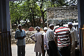 Mourners gather at the gate of the graveyard behind the media HQs in ITO, New Delhi, India. Photo: Sanjit Das/Panos