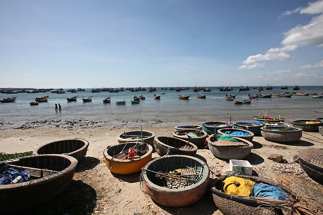 Traditional woven bamboo fishing boats have been pulled ashore, while larger boats sit at anchor in the small harbor in Mui Ne, Vietnam. Nov. 20, 2011.