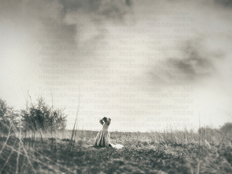 A monochromatic image of a woman in a vintage gown with her hands raised, standing on a field under a cloudy sky.
