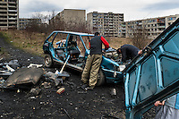 Gipsy men dismantle a used car to recycle metals in the Gipsy ghetto of Chanov on outskirts of Most, Czech Republic, 26 March 2008.