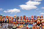 Stock photo of matreshkas russian souvenirs  Colorful set of decorative nesting dolls matreshkas standing in rows on a stall Ukraine Kiev arts and crafts Isolated with a clipping path over blue sky background with copyspace on top