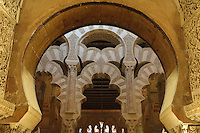 Looking through the horseshoe arch of the mihrab to the maqsura, a richly decorated ribbed vault with small dome, redecorated under Al-Hakam II in 961, with intricately carved interlacing fluted arches, in the Cathedral-Great Mosque of Cordoba, in Cordoba, Andalusia, Southern Spain. The first church built here by the Visigoths in the 7th century was split in half by the Moors, becoming half church, half mosque. In 784, the Great Mosque of Cordoba was begun in its place and developed over 200 years, but in 1236 it was converted into a catholic church, with a Renaissance cathedral nave built in the 16th century. The historic centre of Cordoba is listed as a UNESCO World Heritage Site. Picture by Manuel Cohen