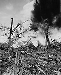 A Marine on left uses a flame thrower to burn an enemy out of a hidden pillbox on Guam. Although the Japanese were surrounded by Marines, they refused to surrender.