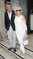 guest & Lulu Kennedy-Cairns.The Prince Albert II of Monaco Olympians Reception, Old Burberry Building, Haymarket, London, England..August 9th, 2012.full length white trousers off the shoulder top purse bag sunglasses shades black grey gray trousers shirt arm around shoulder .CAP/CAN.©Can Nguyen/Capital Pictures.