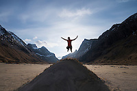 Female hiker jumps in air on sand dune at Horseid beach, Moskenesøy, Lofoten Islands, Norway