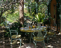 On this shaded patio a garden table has been laid out for an al fresco lunch