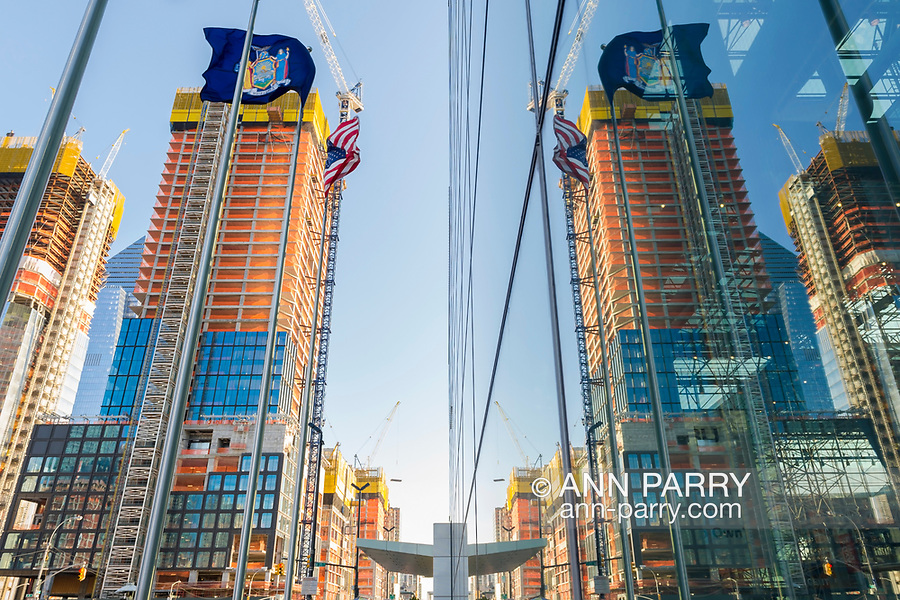 Manhattan, New York, USA. April 12, 2017. Nearby construction at corner or 11th Avenue and W 35th Street is reflected on exterior glass walls of Javits Center on early spring evening.