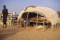 Akadaney, Central Niger, West Africa.  Fulani Nomads.  Fulani Woman alongside her Sleeping Shelter.  Eating and Food Storage Utensils are behind her.