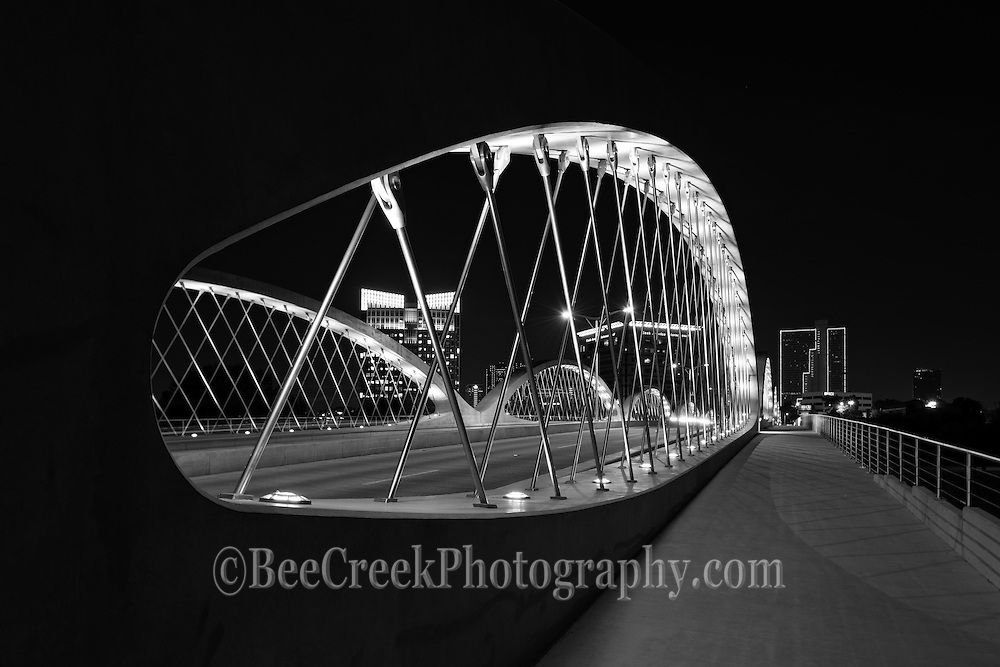 Took this black and white photo of the Seventh Street Bridge in Ft Worth  from the pedestrian walkway at night with the city buildings in the background showing a cityscape.