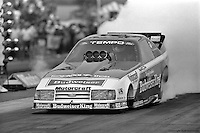 "POMONA, CALIFORNIA: Kenny Bernstein drives his ""Budweiser King"" Ford Funny Car during a 1985 NHRA drag race at Pomona, California."