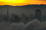 San Francisco's fog underlines a hazy skyline during sunrise as seen from Sausalito, California.