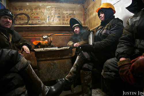 "Men working for the oil and gas prospecting company ""Bashneft"" sit together in the smoking room. Typically, they work in the cold, isolated Arctic tundra for the entire winter, returning to civilisation only in spring."