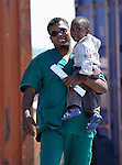 A worker for the Libyan Red Crescent helps the child of migrant workers board a ship in Misrata to take them home to Ghana, Niger, Sudan, or one of several other nearby nations. Even if not fearing for their safety, many of the migrants in Misrata are leaving because the economy of the city, surrounded by troops loyal to strongman Moammar Gadhafi, is at a standstill.