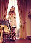 Romantic portrait of a beautiful sensual woman standing at a window, leaning against a rocking chair