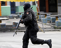 A policeman runs during an operation at Vila Cruzeiro slum, Rio de Janeiro, Brazil, November 25, 2010. Authorities in Rio de Janeiro try to control a fourth day of violence apparently orchestrated by drug gang members who have attacked police stations and burned cars in Rio de Janeiro city as protest by traffickers after being forced from their turf by police occupations of more than a dozen slums in the past two years..(Austral Foto/Renzo Gostoli)