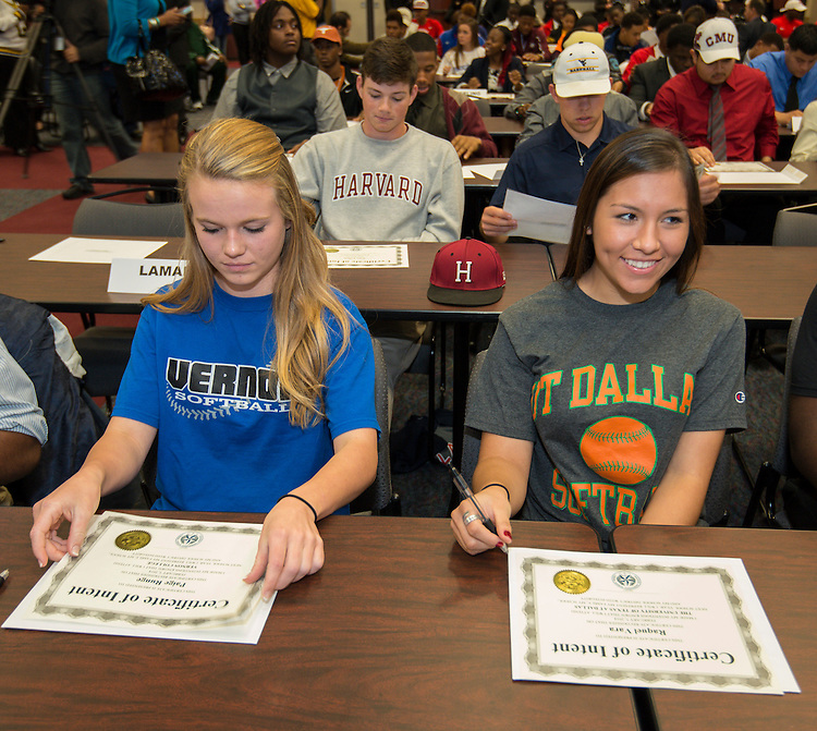 Lamar's Paige Runge (Vernon College), left, and Raquel Vara (UT Dallas) prepare to sign the certificates of intent during a National Signing Day ceremony at the Region 4 Education Center, February 5, 2014.