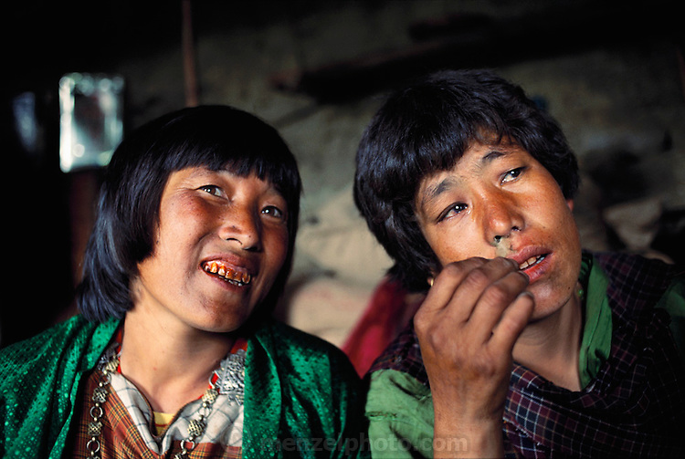 Two women with signs of betel nut damage to their teeth and gums in Shingkhey Village, Bhutan snort finely ground tobacco powder. From Peter Menzel's Material World Project.