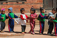 Young children passing by in a procession in the cultural city of Bhaktapur in Nepal