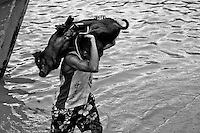 A young Brazilian man carries a tied pig in the riverport, close to Ver-o-Peso market in Belem, Brazil, 3 March 2004. Amazonia is the world's largest dense tropical forest area. Since the 16th century the original indigenous people have been virtually pushed away or exterminated. The primal ancient unity between tribes and the jungle ambient has changed into a fight between the urban based civilization and the jungle enviroment. Although new generations of white and mestizo settlers have not become adapted to the wild tropical climate and rough conditions, they keep moving deeper into the virgin forest. The technological expansion causes that Amazonia is changing rapidly.
