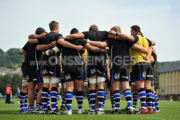The Bath squad huddle together during the pre-match warm-up. Pre-season friendly match, between Bath Rugby and London Welsh on August 11, 2012 at the Recreation Ground in Bath, England. Photo by: Patrick Khachfe / Onside Images