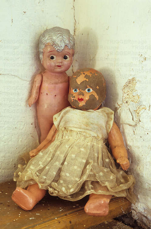 Antique doll in soiled white lacy dress with painted staring blue eyes and red lips but most of her pink flesh paint cracked off sitting on ledge in corner with celluloid naked doll standing next to her