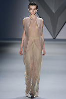 Erjona Ala walks runway in a nude melton cutaway high-low vest over nude silk chiffon sleeveless gown with cowl neck and net lace insets, and nude techno stretch bermuda short, from the Vera Wang Fall 2012 Vis-a-gris collection, during Mercedes-Benz Fashion Week Fall 2012 in New York.