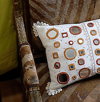 Detail of a mirrored cushion on a sofa upholstered in animal skin