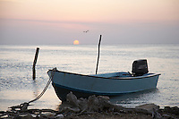 Belize, Central America - Small private skiff tied up on Caye Caulker waterfront with sun setting in backgound.