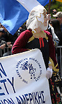 Greek Parade in New York City. A woman in traditional clothing and holding a banner in the Greek Parade in New York City.