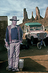 Cardboard cutout poster of John Wayne with the Three Sisters rock formation of Monument Valley in background.