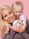 Portrait of a smiling three year old girl with her mother holding a pet rabbit in her hands isolated on pink background