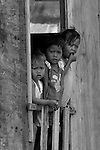 Children watch me pass through Gaya Island Water Village, Malaysia.
