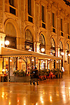 A couple walks through the Galleria at night in Milan, Italy