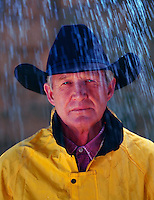 Close up portrait of a man wearing a cowboy hat and raincoat.