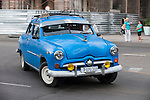 Havana, Cuba; a classic blue 1949 Ford drives down the Paseo de Marti in Havana