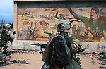 U.S. Army 3rd Division 3-7 infantry soldiers examine a Saddam Hussein mural as they conduct a neighborhood patrol on the outside perimeter of the Baghdad International Airport April 8, 2003.