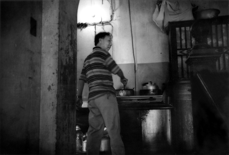 Man making lunch in his hallway kitchen station in the Mao-era style common use area of dilapidated colonial mansion, French Concession, Shanghai, China.  This former mansion is inhabited by over 10 families, all of whom cook at separate kitchen stations in the public area.