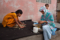 Nafeesa, 27, rolls bidis (indian cigarettes) as her daughter helps to clean up the tobacco leaves and her youngest son, 1 and a half years,  plays near her in her house compound in a slum in Tonk, Rajasthan, India, on 19th June 2012. Nafeesa's health deteriorated from bad birth spacing and over-working. While her husband works far from home, she rolls bidis to make an income and support the family. She single-handedly runs the household and this has taken a toll on her health and financial insufficiencies has affected her children's health. Photo by Suzanne Lee for Save The Children UK