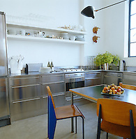 Jean Prouve chairs and a wall lamp by Serge Mouille above a Le Corbusier table in a contemporary  stainless steel kitchen