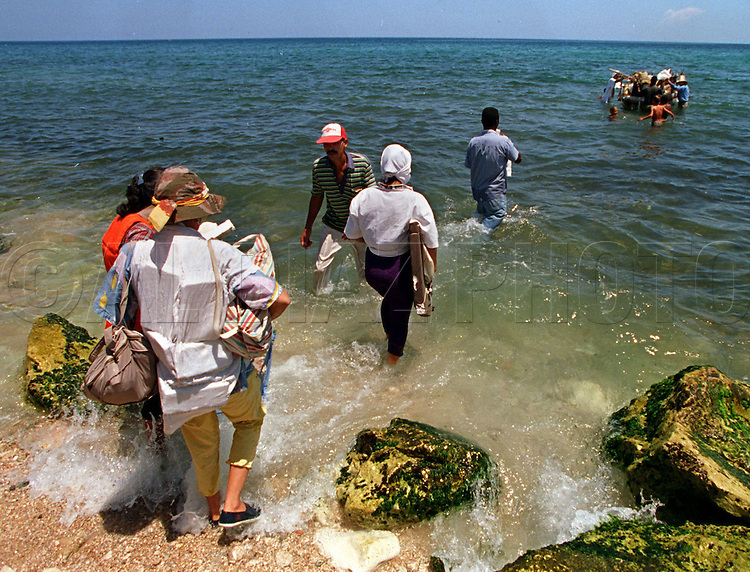 8/1994-Al Diaz/Miami Herald--In 1994 Cuban balseros turned the tiny fishing village of Cojimar into a major point of embarkation for thousands seeking a better life. Here, would-be-Cuban refugees carry small possessions toward an already overcrowded craft preparing to leave from Cojimar.