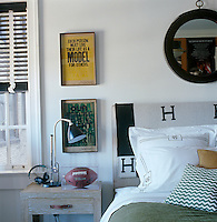 In this boy's bedroom the masculine monogrammed bedlinen and throw on the upholstered headboard are both designs by Hermes