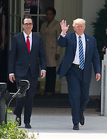 United States President Donald J. Trump waves to US Treasury employees as he walks to the US Treasury Building with US Secretary of the Treasury Steven Mnuchin to sign Executive Orders concerning financial services in Washington, DC on April 21, 2017.<br /> Credit: Ron Sachs / Pool via CNP /MediaPunch
