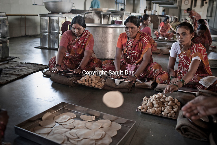 Volunteers and contract labourers are seen making rotis (Indian bread) in the kitchen of the Sai Prasadalaya in Shirdi, Maharashtra, India. The Prasadalaya feeds an approximate number of 30000 Sai Baba devotees as a Prasad (holy meal) every day. Free Prasad meals are served to all the devotees. An approximate number of 1000 devotees are served everyday with this facility. Expenses for a plate of Prasad meal  is around Rs. 15/- but the Saibaba Sansthan provides prasad meals to all Sai devotees to Rs. 6/- only. The prasadalaya at the Shirdi Sai Baba Shrine is powered by a large array of concave mirrors that transform sunlight to energy to create hot water and steam for the cooking process. Photograph: Sanjit Das