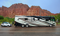 731350274 a massive motor home or recreational vehicle and towed smart car provide transportation for visiting tourists in capitol reef national park utah united states.NOTE: NO PROPERTY RELEASE - FOR EDITORIAL USE ONLY