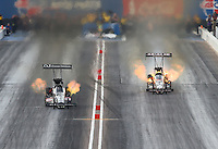 Feb 21, 2015; Chandler, AZ, USA; NHRA top fuel driver Dave Connolly (left) races alongside Terry McMillen on fire during qualifying for the Carquest Nationals at Wild Horse Pass Motorsports Park. Mandatory Credit: Mark J. Rebilas-